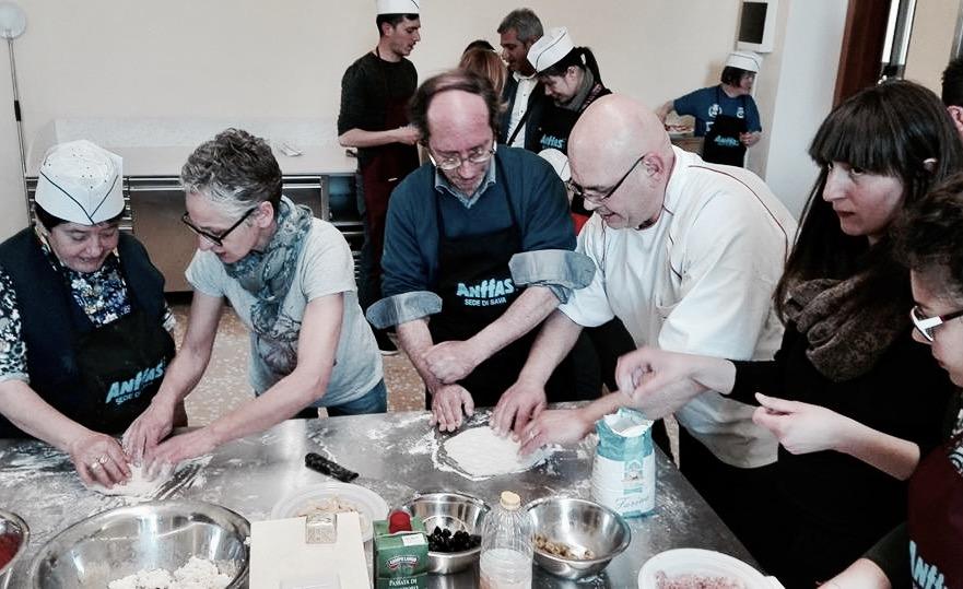 Lo chef Alfredo Garibaldi e i ragazzi i Anffas Sava mentre cucinano