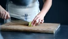 tutti i benefici della cucina e del cucinare - mani che tagliano cipolla con un grosso coltello da cucina, su un tagliere
