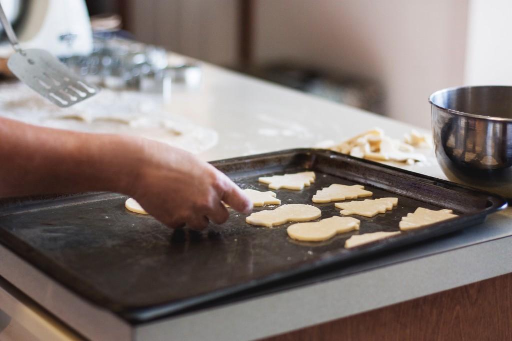 mani che sistemamo dei biscotti da cuocere su una teglia da forno